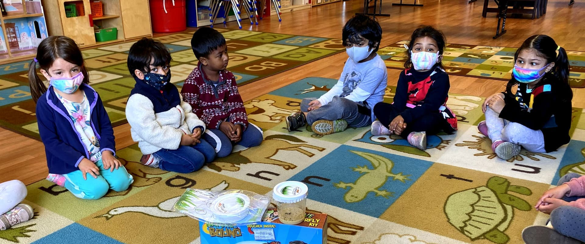 a group of kids sitting and wearing face mask