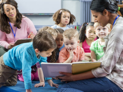 female teacher giving a lesson to nursery students